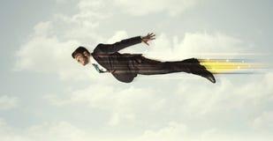 Glücklicher Geschäftsmann, der schnell auf den Himmel zwischen Wolken fliegt Stockfotografie