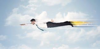 Glücklicher Geschäftsmann, der schnell auf den Himmel zwischen Wolken fliegt Stockfotos
