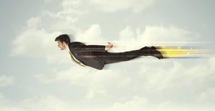 Glücklicher Geschäftsmann, der schnell auf den Himmel zwischen Wolken fliegt Lizenzfreies Stockfoto