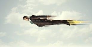 Glücklicher Geschäftsmann, der schnell auf den Himmel zwischen Wolken fliegt Stockbild
