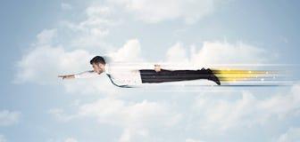 Glücklicher Geschäftsmann, der schnell auf den Himmel zwischen Wolken fliegt Lizenzfreies Stockbild