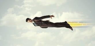 Glücklicher Geschäftsmann, der schnell auf den Himmel zwischen Wolken fliegt Stockbilder