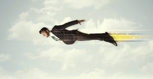 Glücklicher Geschäftsmann, der schnell auf den Himmel zwischen Wolken fliegt Lizenzfreie Stockfotografie