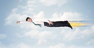 Glücklicher Geschäftsmann, der schnell auf den Himmel zwischen Wolken fliegt Lizenzfreie Stockfotos