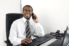 Glücklicher Geschäftsmann, der am Schreibtischlächeln arbeitet Lizenzfreie Stockbilder