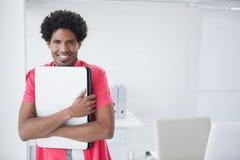 Glücklicher Geschäftsmann, der seinen Laptop anhält Lizenzfreie Stockfotos