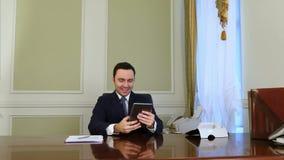 Glücklicher Geschäftsmann, der selfie Foto mit moderner Tablette und dem Lächeln macht stock footage