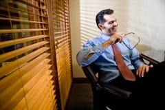 Glücklicher Geschäftsmann, der am Sitzungssaaltisch sitzt Lizenzfreie Stockbilder