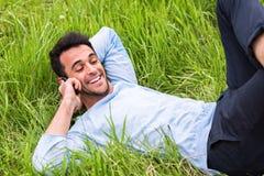 Glücklicher Geschäftsmann, der am Telefon liegt auf dem grünen Gras spricht stockbilder