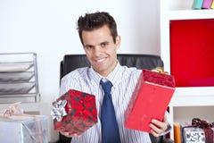 Glücklicher Geschäftsmann, der Weihnachtsgeschenke gibt Stockbild