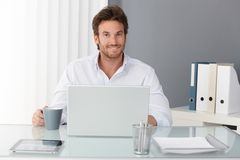 Glücklicher Geschäftsmann im Büro Stockfotos