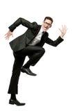 Glücklicher Geschäftsmann läuft in schwarze Klage auf Weiß. lizenzfreie stockfotografie