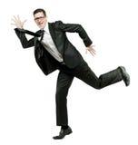 Glücklicher Geschäftsmann läuft in schwarze Klage auf Weiß. Stockfoto