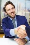Glücklicher Geschäftsmann mit der Klage, die Hand zum neuen Partner-Verhältnis gibt lizenzfreie stockfotografie
