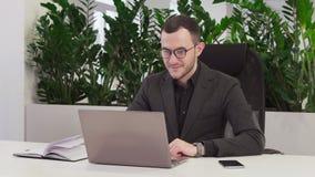 Glücklicher Geschäftsmann mit Gläsern betrachtet den Laptop stock footage