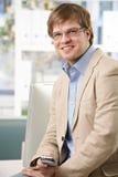 Glücklicher Geschäftsmann mit Handy im Büro lizenzfreie stockfotografie
