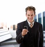 Glücklicher Geschäftsmann mit Mobiltelefon stockbild