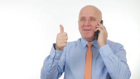 Glücklicher Geschäftsmann Talking zum Mobile machen enthusiastische Handzeichen lizenzfreie stockfotos