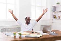 Glücklicher Geschäftsmanngewinn Sieger, schwarzer Mann im Büro lizenzfreie stockbilder