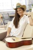 Glücklicher Gitarrist, der auf Sofa sitzt Stockbild