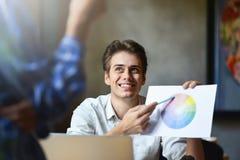 Glücklicher Grafikdesigner, der Farbdiagramm in seiner Hand hält lizenzfreie stockbilder