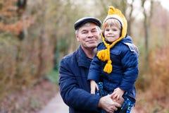 Glücklicher Großvater mit seinem Enkelkind auf Arm lizenzfreie stockfotos