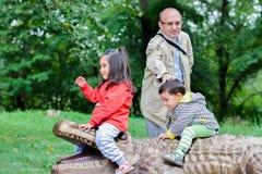 Glücklicher Großvater und kleine Enkelkinder, die im Zoo spielen Stockfotografie