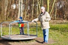 Glücklicher Großvater und sein kleiner Enkel, die Spaß auf altem Spiel hat lizenzfreie stockfotos
