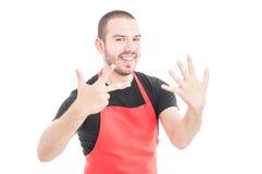 Glücklicher Grossmarktverkäufer, der acht Finger zeigt Lizenzfreie Stockbilder