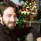 Glücklicher gut aussehender Mann mit blauen Augen und dem langen Bart und Haar zu Hause Lächeln Heiliger Nacht stockbild