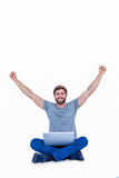 Glücklicher gutaussehender Mann, der hinter seinem Computer zujubelt Lizenzfreie Stockfotografie