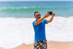 Glücklicher hübscher lächelnder Mann im Urlaub, der über den Strand nimmt selfie lacht Lizenzfreies Stockfoto