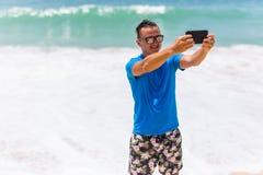 Glücklicher hübscher lächelnder Mann im Urlaub, der über den Strand nimmt selfie lacht Stockbild
