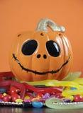 Glücklicher Halloween-Jack-O-Laternenkürbis auf Süßigkeit - vertikale Nahaufnahme Stockfotografie