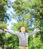 Glücklicher Herr, der seine Arme verbreitet und aufwärts in einem Park schaut Stockbilder