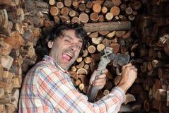 Glücklicher Holzfäller, der die Axt schärft Lizenzfreies Stockbild
