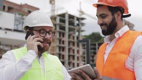 Glücklicher Ingenieur spricht am Handy auf Baustelle und überprüft die Arbeit der Arbeitskraft Erbauergespräche an stock footage