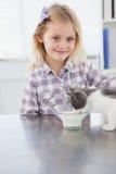 Glücklicher Inhaber, der ihre Trinkmilch der Katze streichelt Lizenzfreie Stockfotos