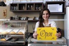 Glücklicher Inhaber eines geöffneten Zeichens der Kaffeevertretung Stockfotos