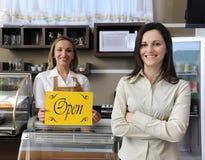 Glücklicher Inhaber eines geöffneten Zeichens der Kaffeevertretung Stockfotografie