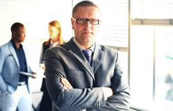 Glücklicher intelligenter Geschäftsmann mit Team verbindet die Diskussion im Hintergrund lizenzfreie stockfotos