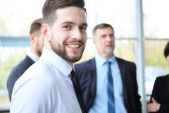 Glücklicher intelligenter Geschäftsmann mit Team verbindet die Diskussion im Hintergrund lizenzfreies stockbild
