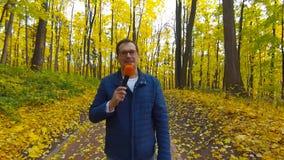 Glücklicher Journalist berichtet vom Herbstpark für Fernsehen stock footage