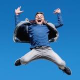 Glücklicher jugendlich Junge, der gegen klaren Himmel springt Lizenzfreie Stockfotos