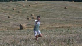 Glücklicher jugendlich Junge, der mit Papierflugzeug vor dem hintergrund des geernteten Feldes spielt stock footage