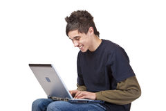 Glücklicher Jugendlicher am Computer, der das Internet surft Lizenzfreies Stockbild
