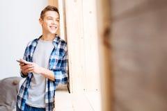 Glücklicher Jugendlicher, der heraus das Fenster schaut Lizenzfreie Stockfotografie