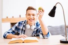 Glücklicher Jugendlicher, der am Tisch mit einem Apfel sitzt Lizenzfreies Stockbild