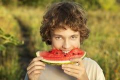 Glücklicher Jugendlicher, der Wassermelone isst Lizenzfreies Stockbild