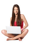 Glücklicher Jugendlicher mit dem Laptop, der auf weißem Hintergrund sitzt Stockfotos